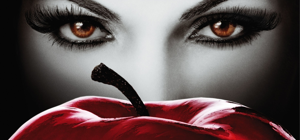 Regina looks evilly over the top of a scarlet apple