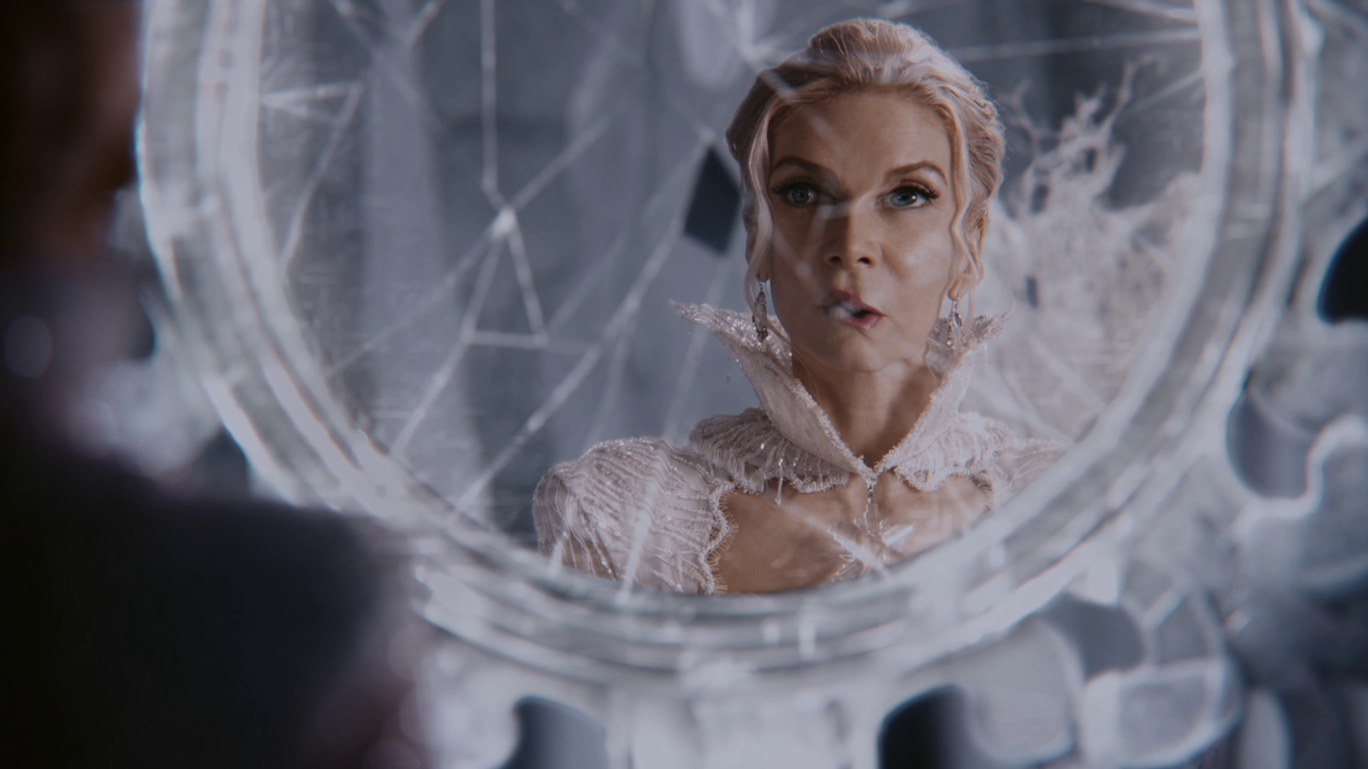 The Snow Queen looks at her broken mirror.